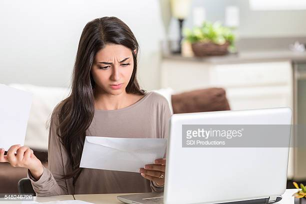 Distraught woman paying her bills at home