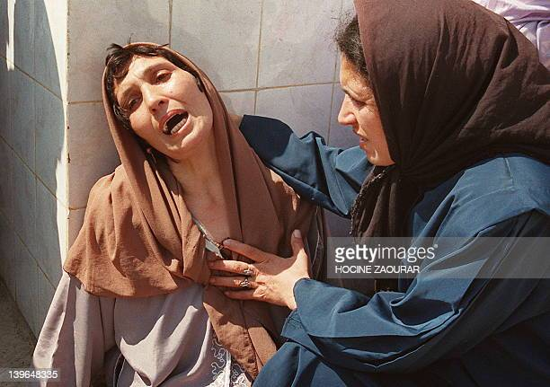 Distraught woman who has lost several close members of her family is comforted 23 September 1997 by a relative who lost her parents, at Zmirli...