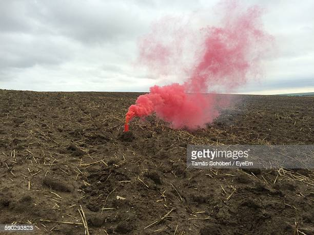 Distress Flare On Field Against Cloudy Sky
