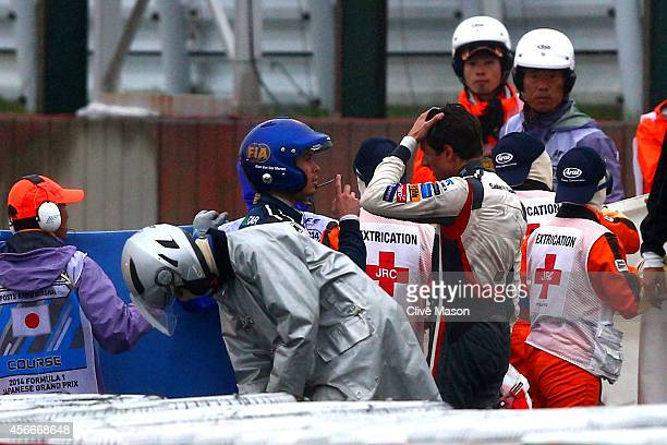 A distressed Adrian Sutil of Germany and Sauber F1 speaks to a Doctor whilst Jules Bianchi of France and Marussia receives urgent medical attention...