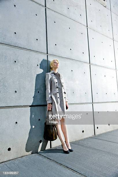Distressed business woman leaning against wall