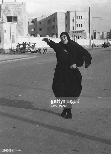 Distressed Egyptian woman chasing the cart carrying the body of her dead son through the streets of Port Said, the town occupied by Anglo-French...
