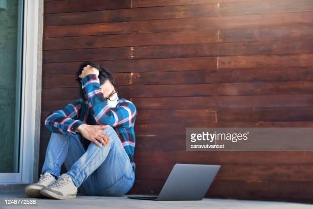 distressed man sitting on ground with his laptop during lockdown - wanhoop stockfoto's en -beelden