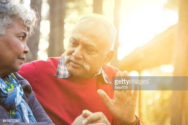 Distressed senior adult couple talk at outdoor park.