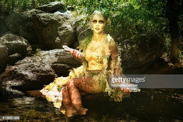 Distressed water nymph picks up plastic waste from stream