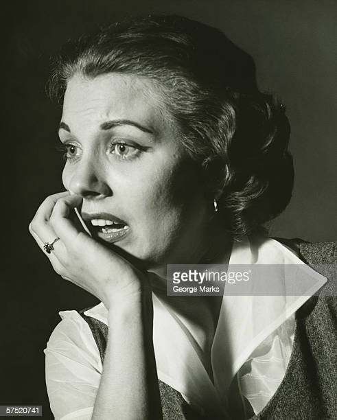 Distressed woman posing in studio, (B&W), portrait