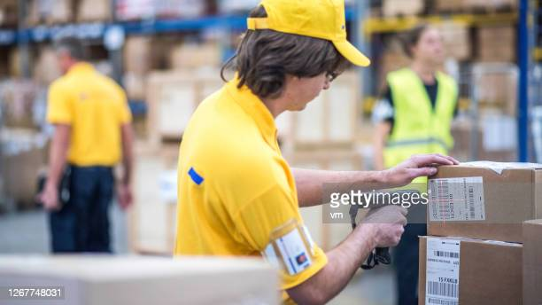 distribution center employee scanning a package with a bar code reader - post structure stock pictures, royalty-free photos & images