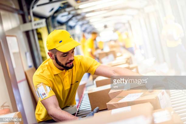 distribution center worker handling cardboard packages - post structure stock pictures, royalty-free photos & images