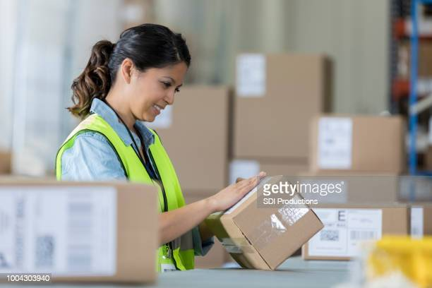 Distribution warehouse employee prepares package