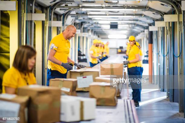 Distribution warehouse employees examining boxes on a conveyor belt