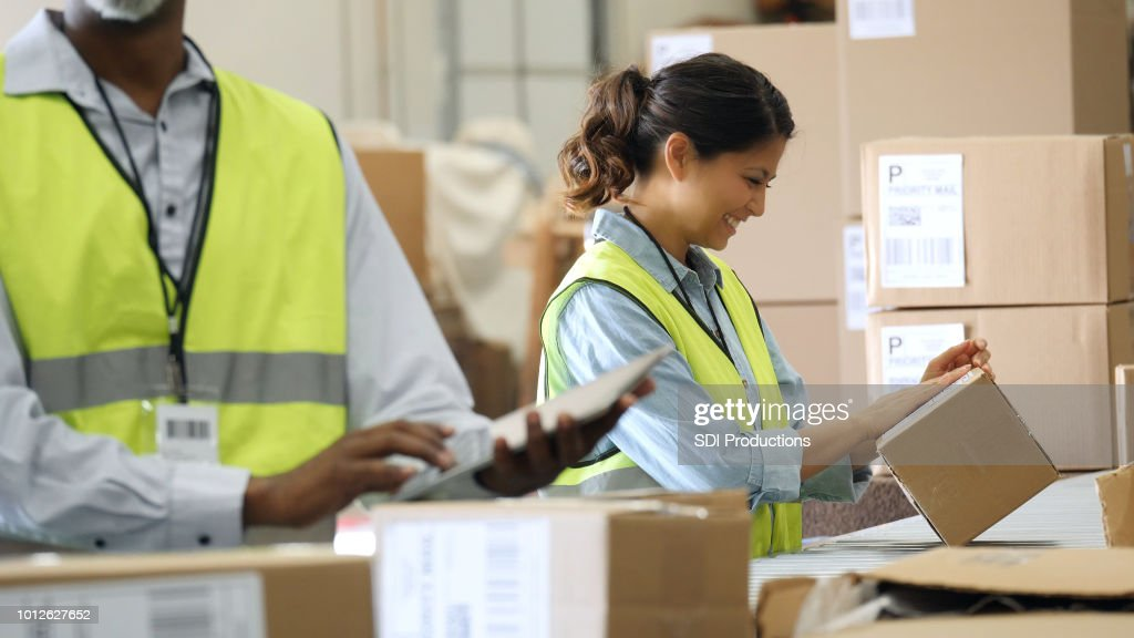Distribution warehouse employees prepare packages for shipment : Stock Photo