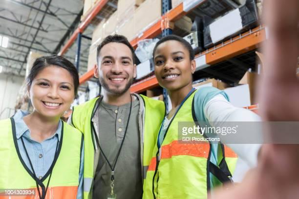 Distribution warehouse employees take selfie