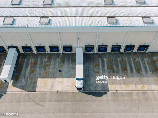 distribution warehouse with loading docks and trucks as seen from above - haulage stock pictures, royalty-free photos & images