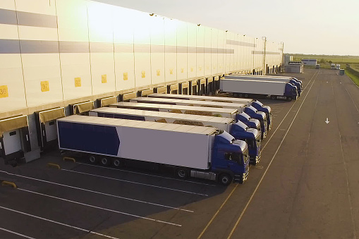 distribution warehouse with trucks awaiting loading 1162624331