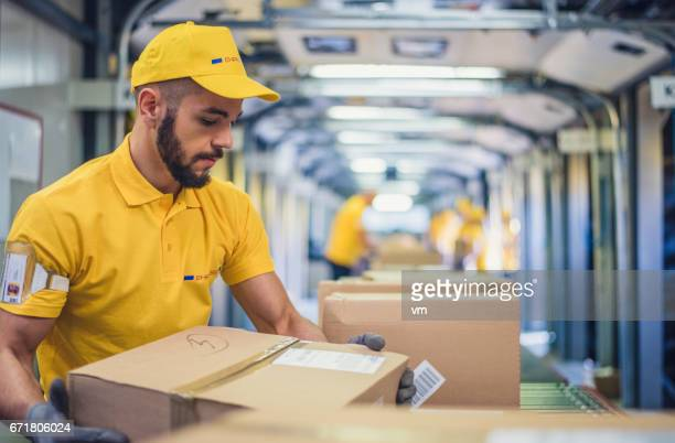 distribution warehouse worker holding a box - post structure stock photos and pictures
