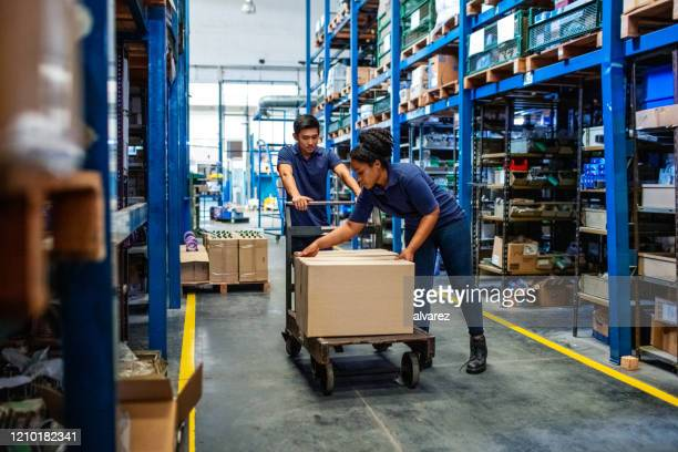 distribution warehouse workers moving boxes in plant - sack barrow stock pictures, royalty-free photos & images