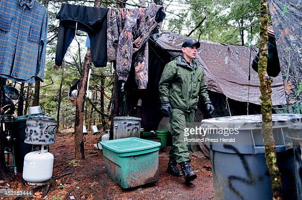 District Game Warden Aaron Cross exits Christopher Knight's camp Tuesday April 9 2013 in a remote wooded section of Rome after police inspected the...