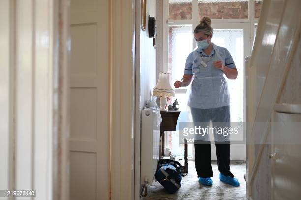 District nurse Rebecca McKenzie dons personal protective equipment as she visits 86-year-old Margaret Ashton during a home visit on June 9, 2020 in...