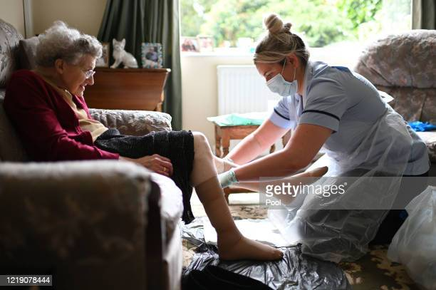 District nurse Rebecca McKenzie , wearing personal protective equipment changes the dressings on the legs of 86-year-old Margaret Ashton to treat her...