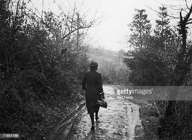 District Nurse Tithecott of Glynneath South Wales carries her black bag of medical supplies down a country lane during her rounds 6th June 1942...