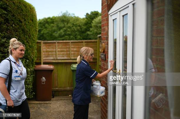District nurses Emma Fiello and Rebecca McKenzie knock on a door as they carry out home visits in Grimsby, northeast England on June 9, 2020.