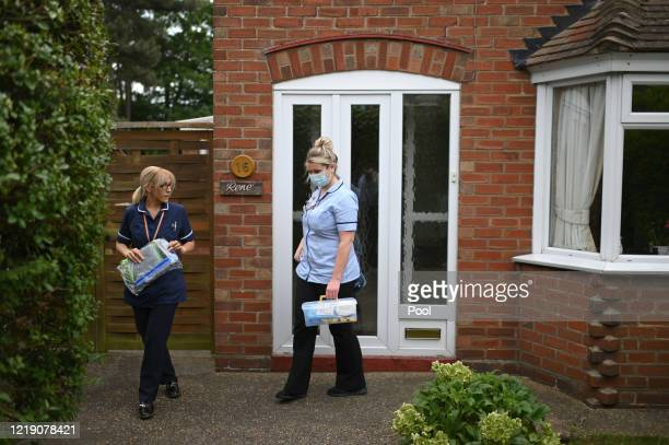District nurses Rebecca McKenzie and Emma Fiello leave the house of 86-year-old patient Margaret Ashton after a home visit on June 9, 2020 in...