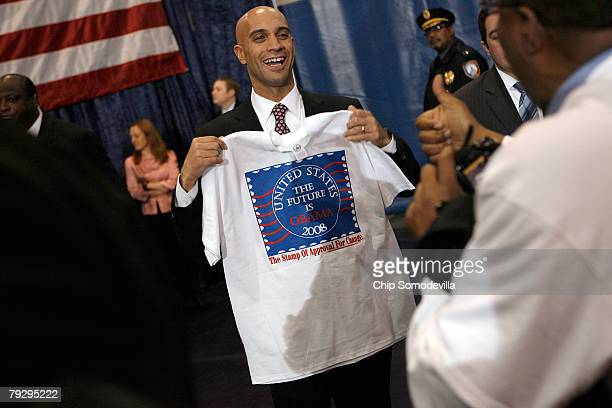 District of Columbia Mayor Adrian Fenty poses for photographs with a tshirt supporting Sen Barack Obama during a rally in the Bender Arena at...