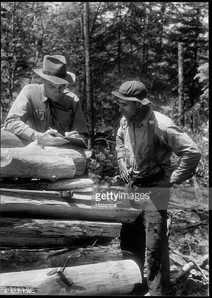 District Ranger William Brown discusses the terms of a timber sales contract with businessman George Jones. Hiawatha National Forest, Michigan. |...
