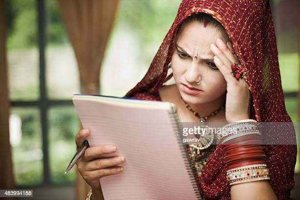 Disturbed newly married Indian, young woman reading on notepad.