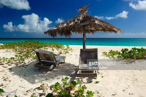 disused loungers and umbrella on pink sand beach, barbuda, antigua & barbuda - harbor island bahamas stock photos and pictures