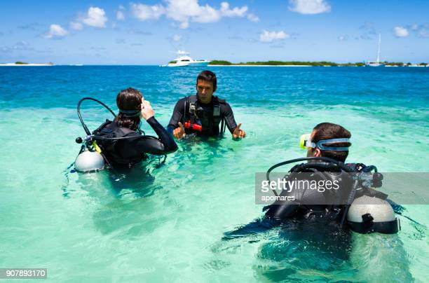 Dive master training a couple for first dive in a tropical turquoise island beach.