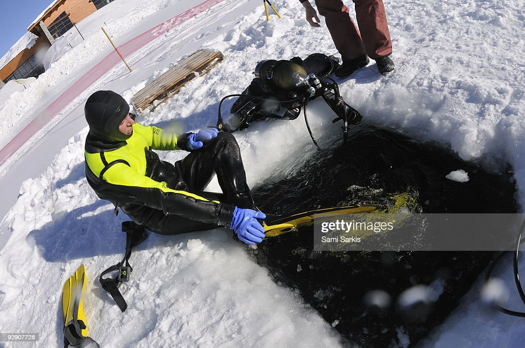Diver about to dive through an ice hole : Stock Photo