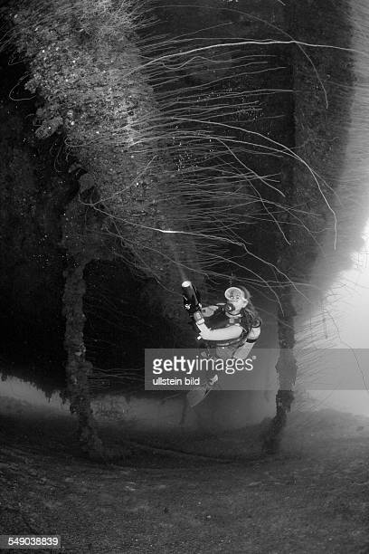 Diver at massive 16-inch 45 Caliber Gun under the HIJMS Nagato Battleship, Marshall Islands, Bikini Atoll, Micronesia, Pacific Ocean