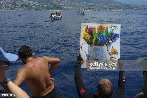 A diver carries a painting in an attempt to break the Guinness world record of the number of paintings underwater off the coast of Jounieh on June 3...