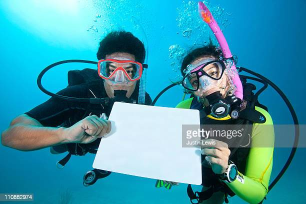 diver couple holding blank sign underwater. - blank sign stock photos and pictures