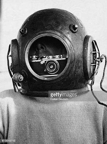 A diver demonstrates how he took photographs of the wreck of the Thetis by strapping a Leica camera inside his helmet and holding the trigger between...