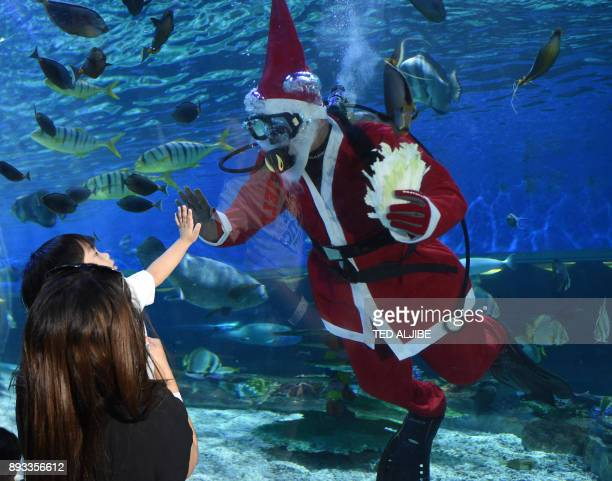Diver dressed in a Santa Claus costume greets a mother and child while feeding fish inside an aquarium of the Ocean park in Manila on December 15,...