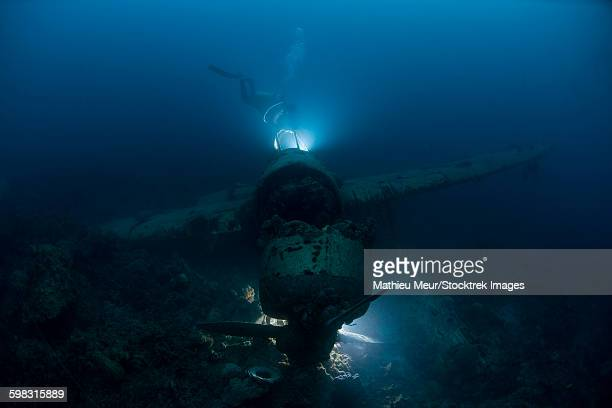 Diver exploring the wreck of a Japanese Navy Seaplane in Palau, Micronesia.