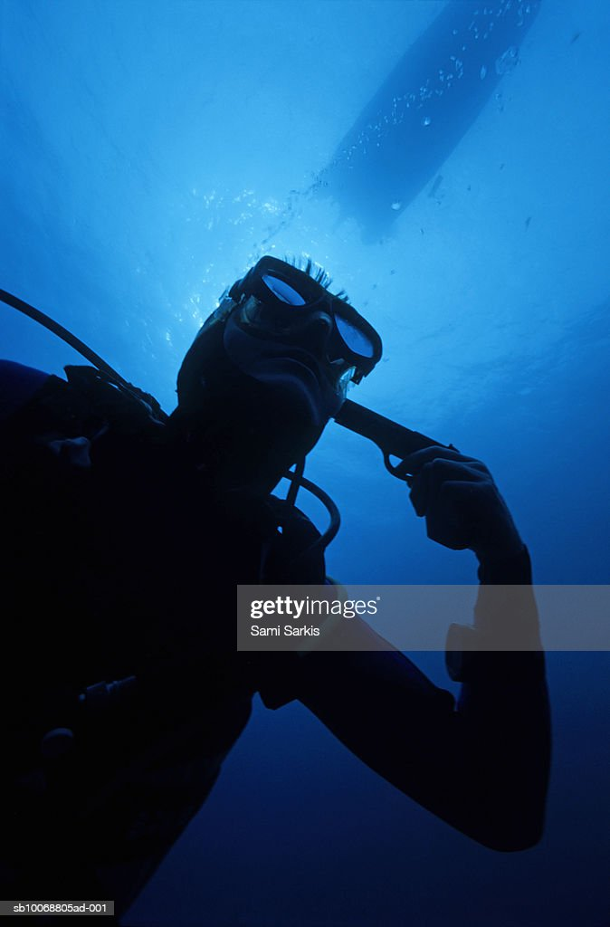 Diver holding gun to head, underwater, low angle view : Stock Photo