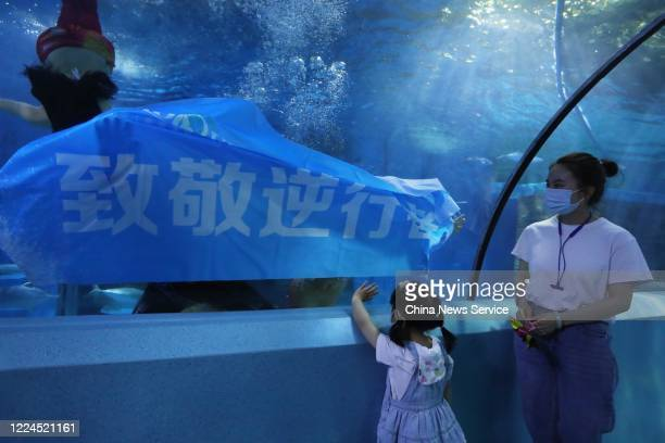 A diver holds a slogan of pay tribute to medics at Nanjing Underwater World on May 12 2020 in Nanjing Jiangsu Province of China Nanjing Underwater...