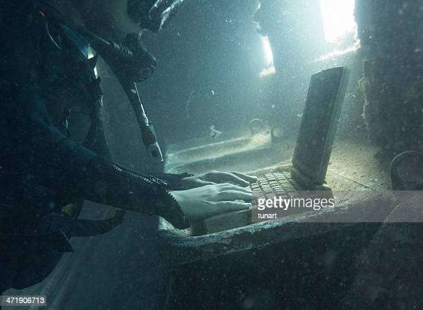 Diver in a submerged and ruined airplane using laptop
