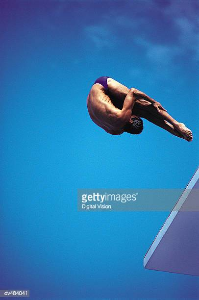 Diver in pike position off of platform