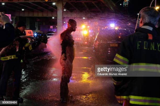 FDNY diver is sprayed with water after attending a call of a helicopter crashed in the East River on March 11 2018 in New York City According to...
