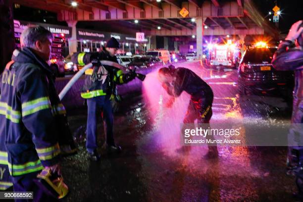 FDNY diver is sprayed with water after attending a call of a helicopter crash in the East River on March 11 2018 in New York City According to...