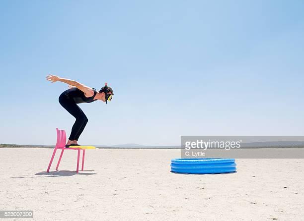 diver jumping into kiddie pool in desert - clumsy stockfoto's en -beelden