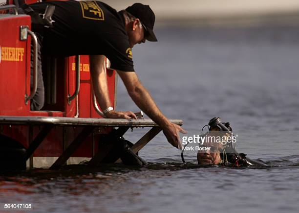–Diver Keith Prinzing with the Orange County Sheriff's Department Bomb Squad hands several blasting caps off to fellow investigator Steve Garrison...