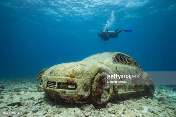 A diver kicks past a to scalesized underwater statue of a volkswagon beetle at MUSA off the coast of Isla Mujeres Mexico on September 26 2018...
