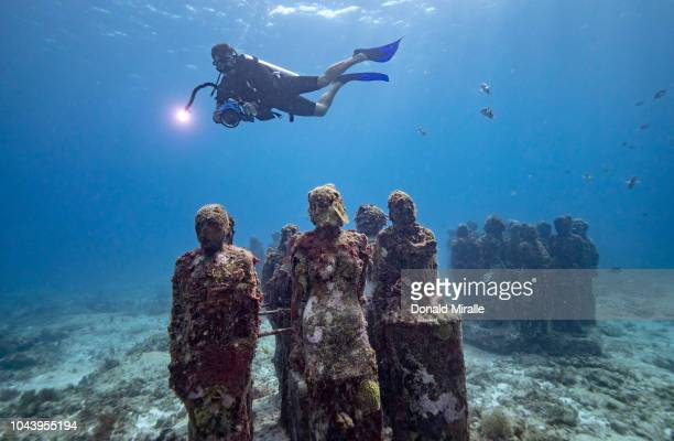 A diver kicks past the underwater statues at MUSA off the coast of Isla Mujeres Mexico on September 26 2018 Consisting of over 500 permanent...