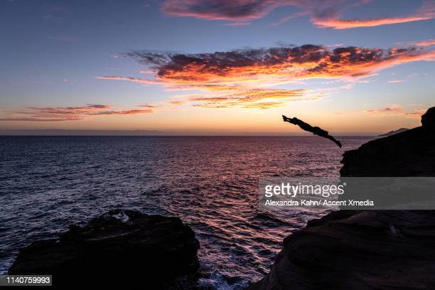 diver launches from cliff into ocean at sunset - leap of faith stock photos and pictures