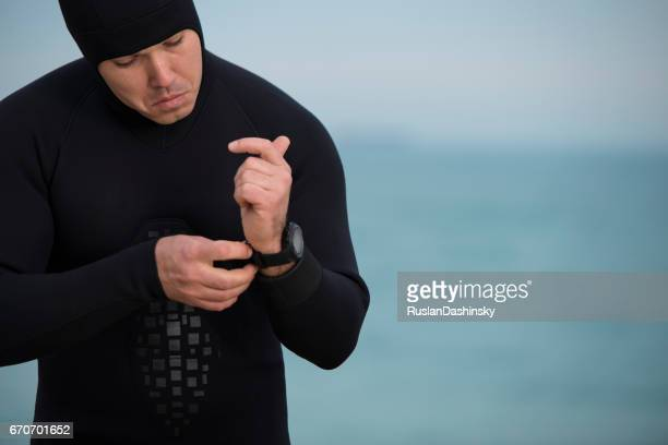 diver man putting on waterproof watch. - aqualung diving equipment stock pictures, royalty-free photos & images